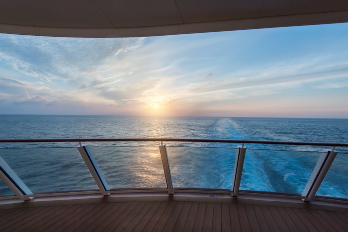 Scenic view of a cruise ship's wake seen from the deck at sunrise.