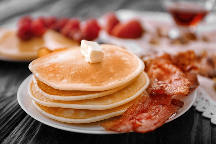 Four pancakes with a pat of butter on top, sharing a plate with some pieces of bacon