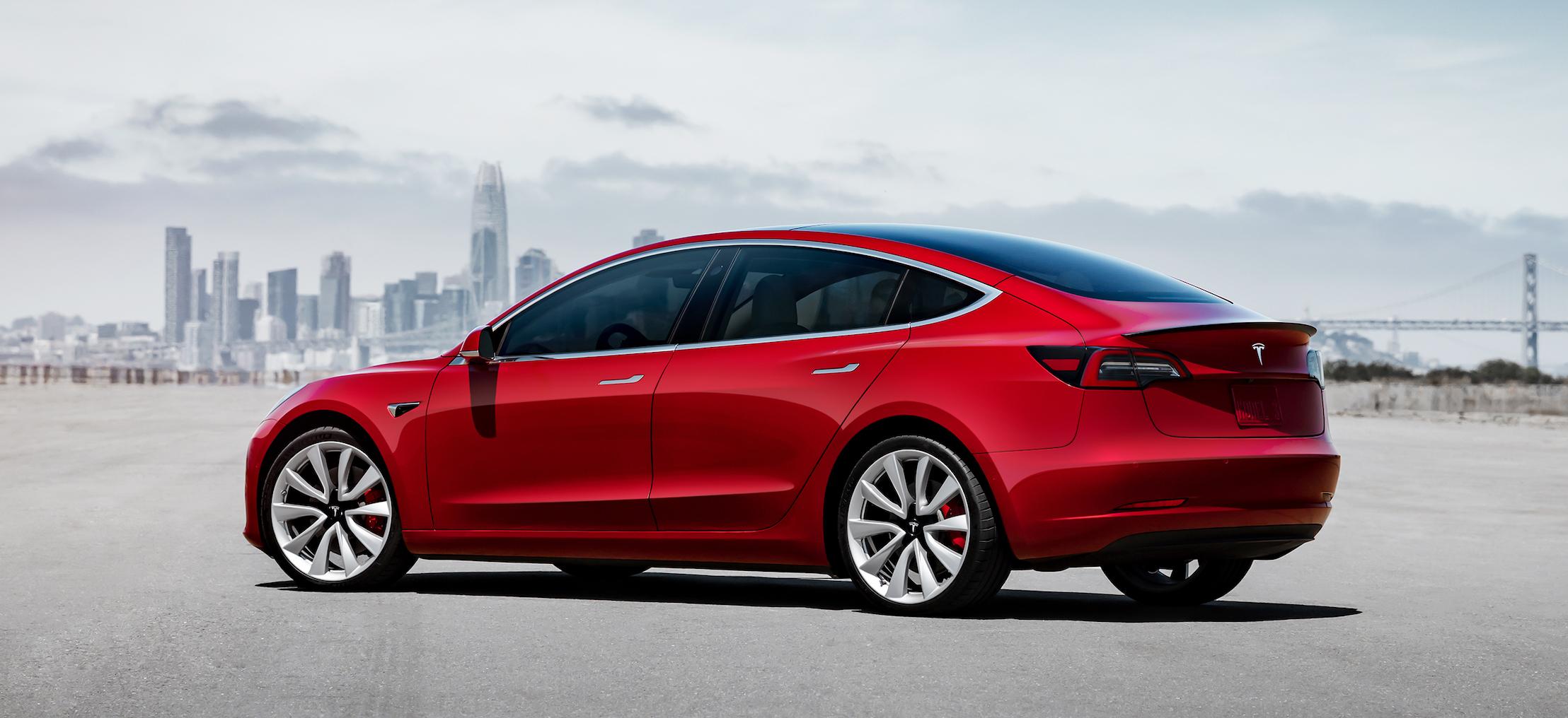 A red Tesla Model 3, a sleek compact luxury-sports sedan