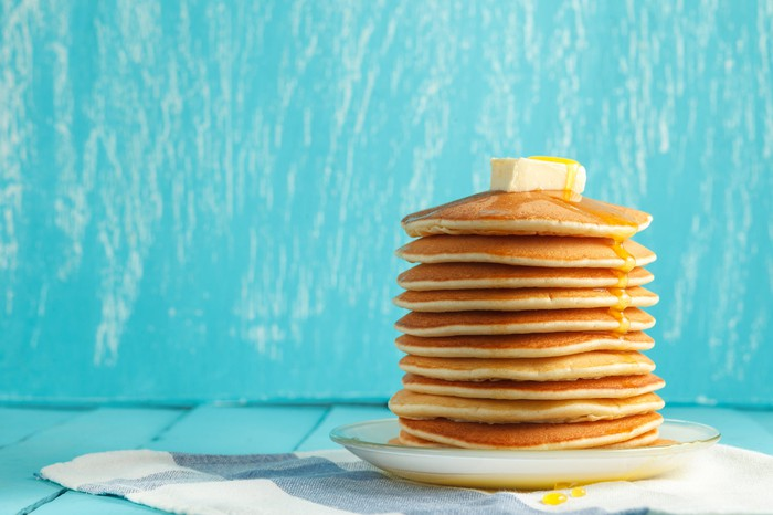 High stack of pancakes on a plate with butter and honey set against a turquoise backdrop.