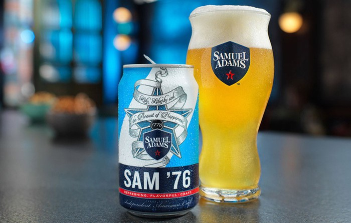 Sam 76 beer can next to a Samuel Adams glass of beer.