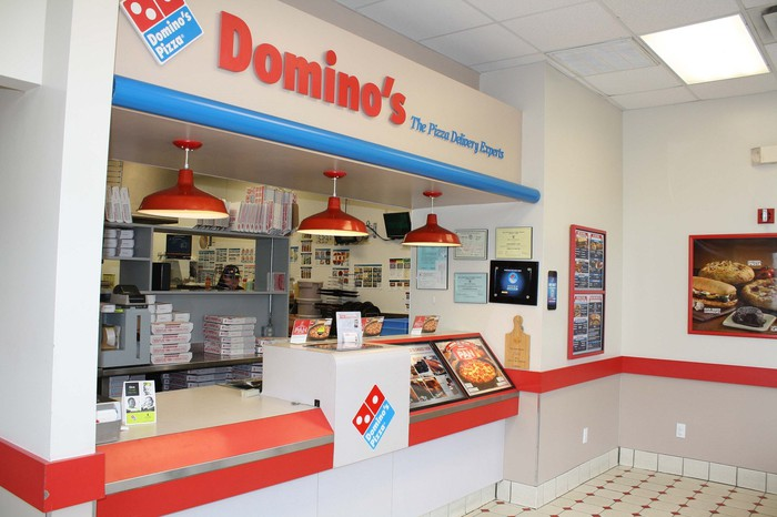 Inside of Domino's store with counter, heat lamps, logo, and display materials.