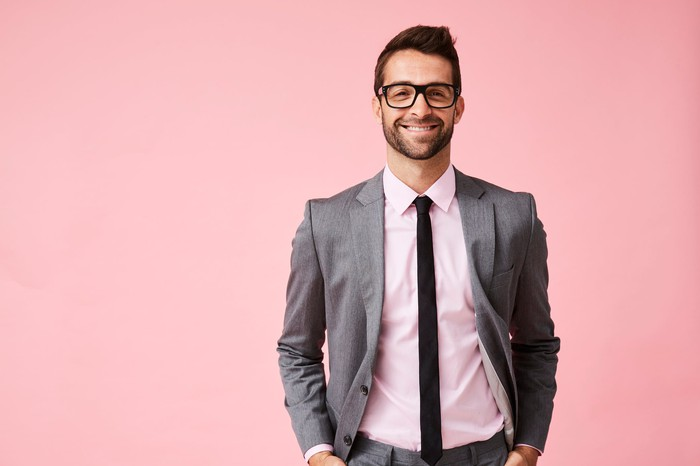 Smiling man in suit against pink background.