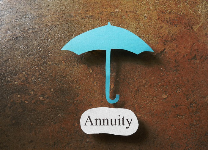 A blue paper cutout of an umbrella is shown, with the word annuity printed on a bit of white paper below it.