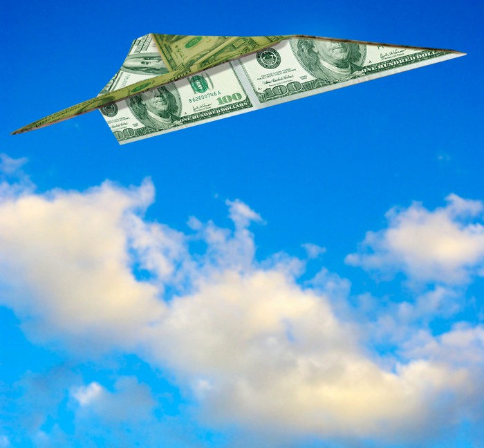 A paper airplane folded out of a $100 bill is flying against a blue sky.