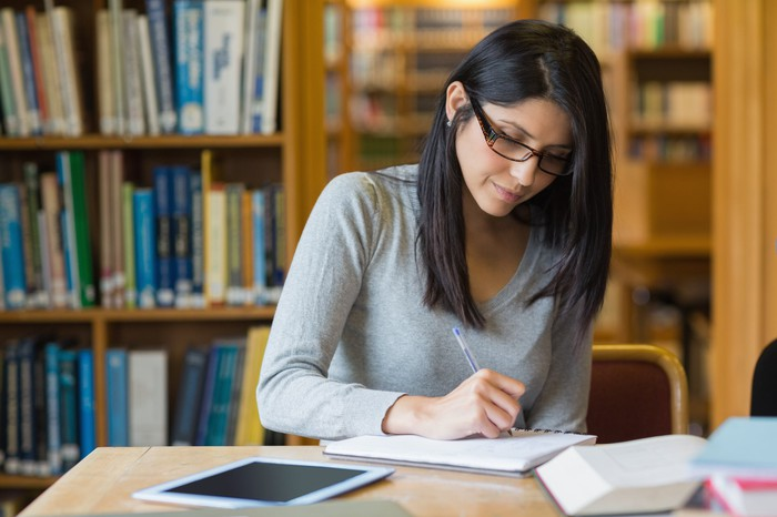 A woman writes on a piece of paper as she sits in a library