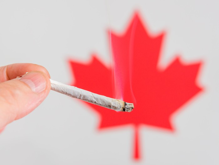 A lit cannabis joint being held in front of a red Canadian maple leaf.