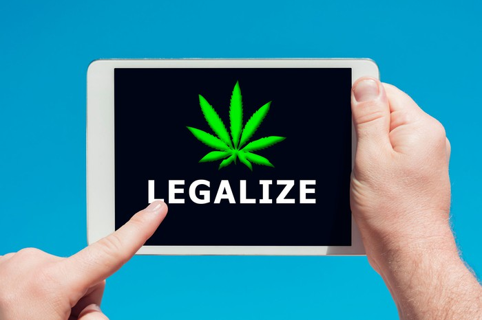 """A person holding a tablet and touching the screen, which says the word """"legalize"""" and has a cannabis leaf above the word."""