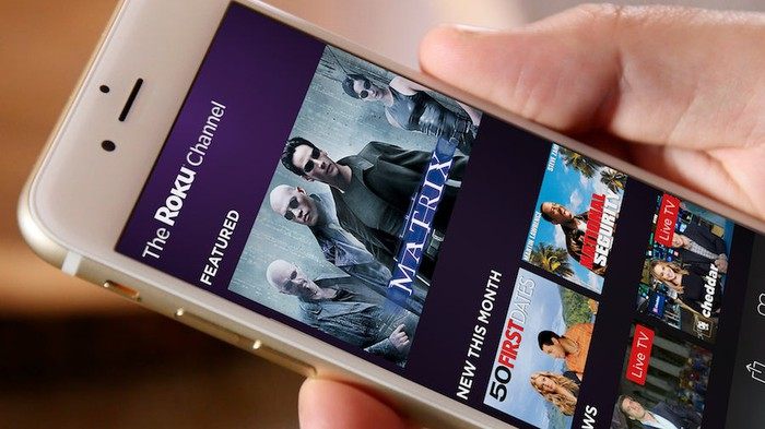 A hand holding a smartphone displaying the Roku app.