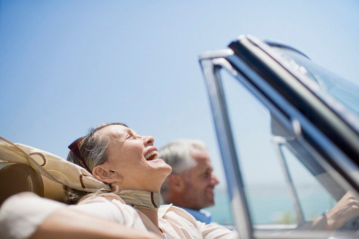 Older man and woman smiling in a convertible.