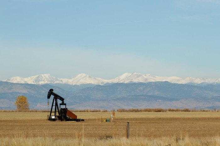 An oil pump jack with the mountains in the background.