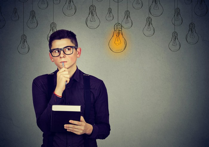 "A man in glasses holding a pen to his mouth with lightbulbs drawn on the background; one lightbulb is yellow, or ""on"""