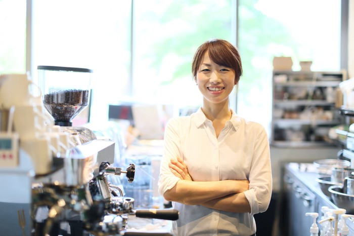 A female entrepreneur stands near the espresso machine in her coffee shop.