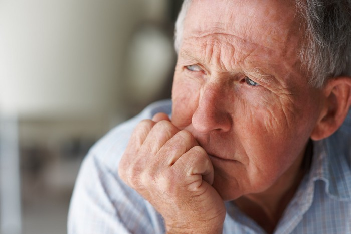 A visibly worried senior man looking out a window, with his chin resting on his balled fist.