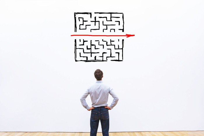 Business man staring at a red straight, arrow crossing a complicated labyrinth.