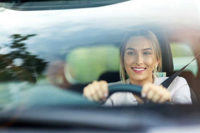 Woman driving a car, smiling