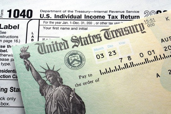 A U.S. Treasury federal refund check lying atop IRS tax form 1040.