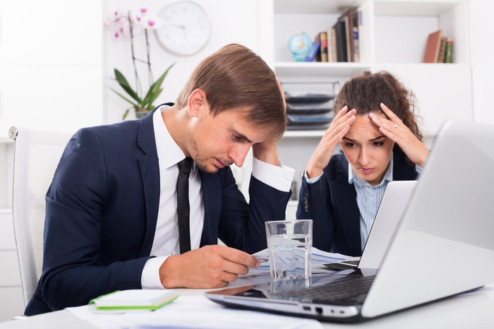 Professionally dressed man and woman at laptop, holding their heads