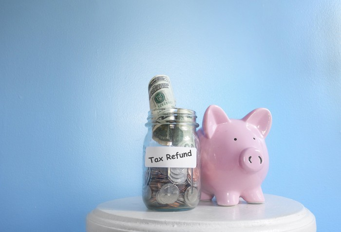 Glass jar with coins and rolled-up bills labeled tax refund next to a pink piggy bank