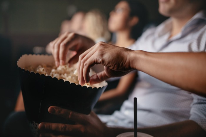 Two hands reach into a large bag of popcorn in a movie theater.