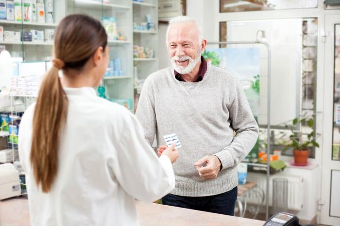 Happy senior male customer buying medications at drugstore