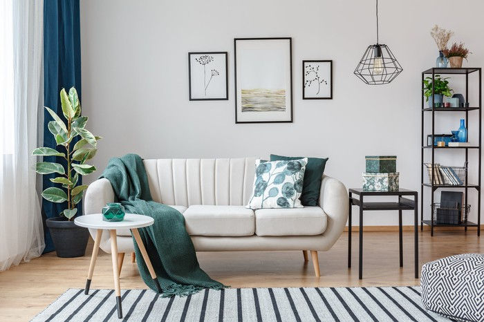 A modern living room, with a couch, two small tables, a potted plant, and a pendant lamp