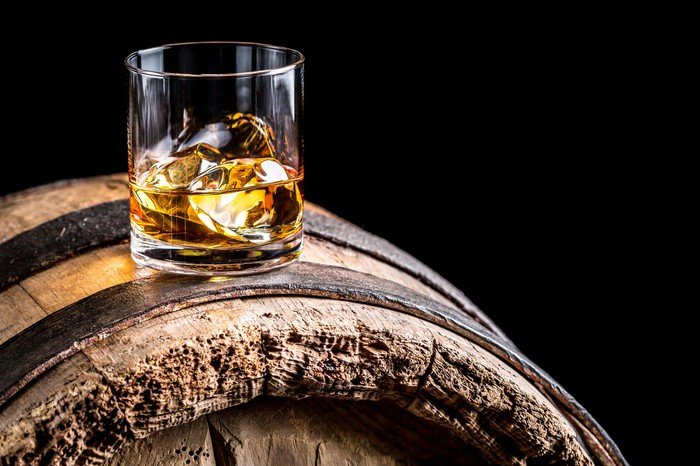 Rocks glass with whiskey and ice cubes in it sitting on a whiskey barrel