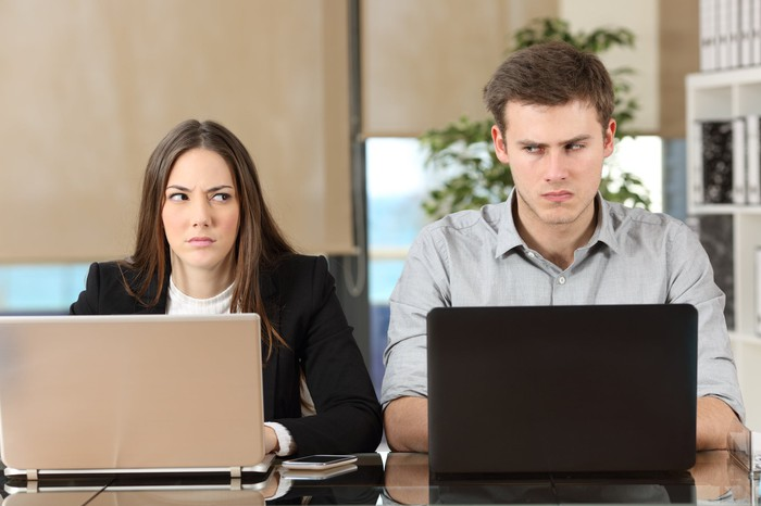 A woman and a man shoot each other looks as they sit side by side at laptops.