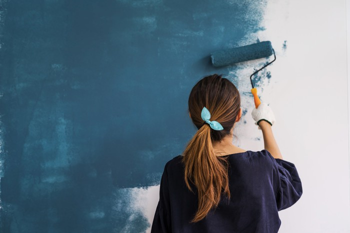 A woman painting a white wall in blue paint with a paint roller.