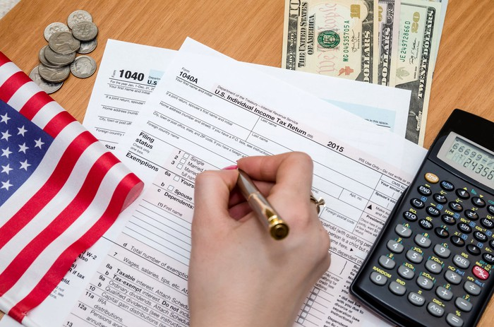 Person filling out tax form.