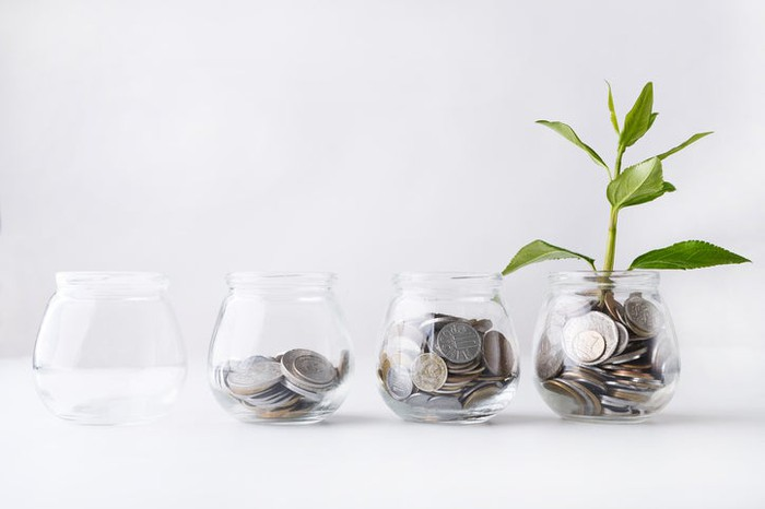 A row of glass jars, each with successively more coins, and the last with a plant growing out of it.