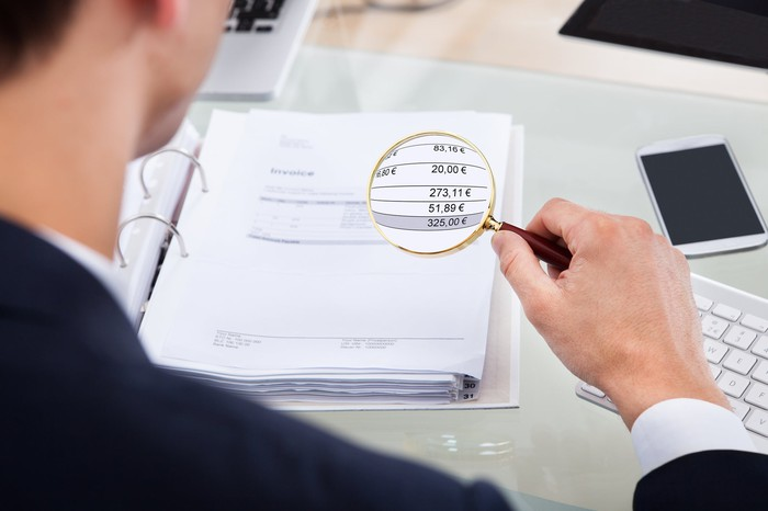 Person holding magnifying glass over financial ledger