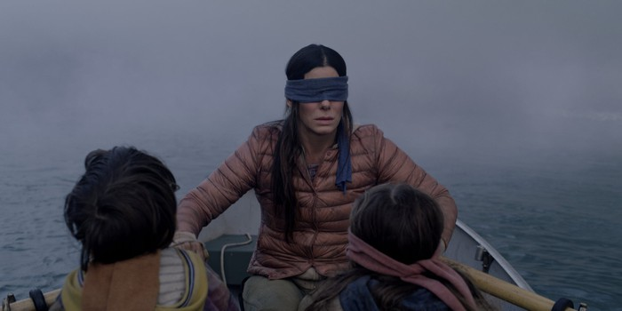 """A still from """"Bird Box"""": a woman wearing a blindfold rowing a rowboat with two blindfolded children"""