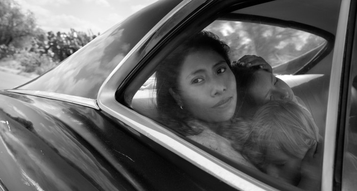 """A still from """"Roma"""": a woman in the back of a car, looking out the window, with two children asleep on her lap"""
