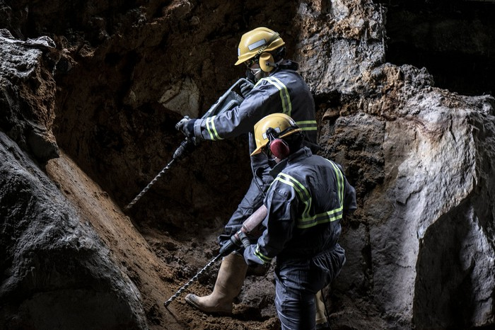 A pair of workers in helmets carrying drills in a subterranean environment