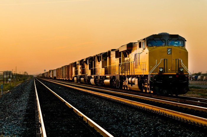 A freight train next to two empty train tracks