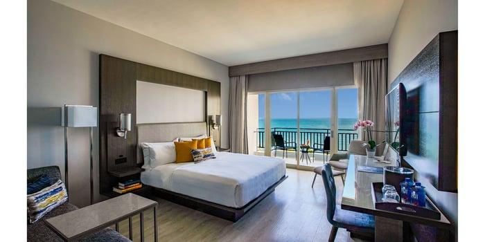 A sleek, minimalist hotel room facing tropical waters.