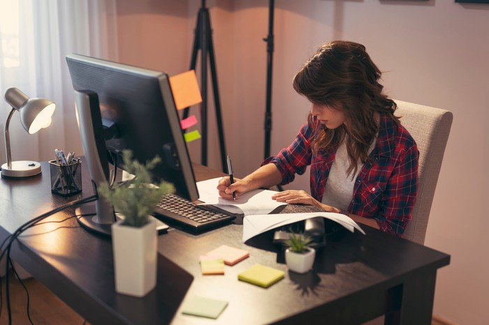 A woman sitting at an office desk takes notes in front of a computer.