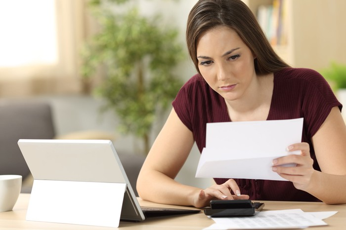 A woman seated at a desk looks at a document while using a calculator.