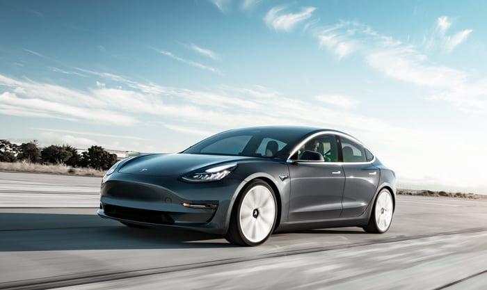 A dark gray Tesla Model 3, a compact luxury sports sedan.
