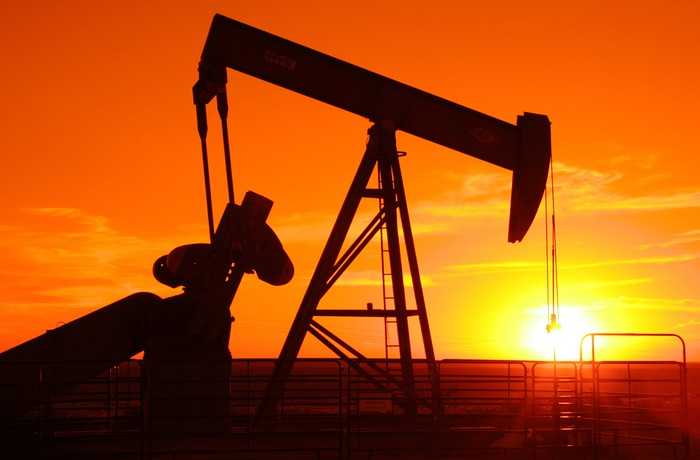 An oil pump jack with orange sunset in the background.