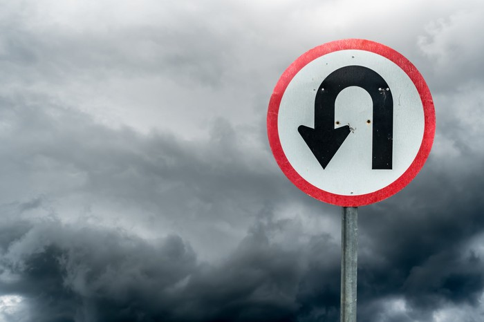 U-turn sign against a cloudy backdrop