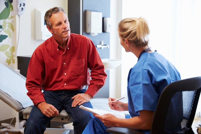 Person wearing scrubs talking to another person in an exam room.
