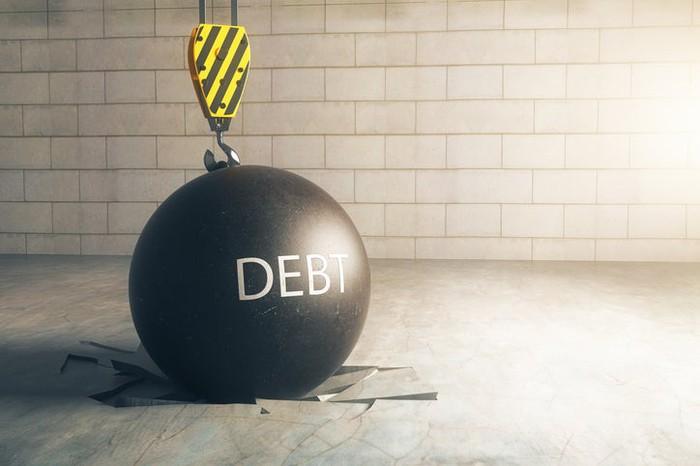 """A wrecking ball with the word """"debt"""" written on it."""