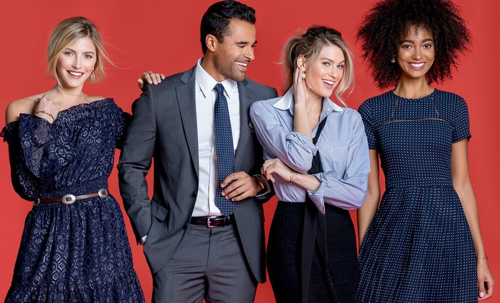 Three women and one man fashionably dressed smiling and posing.