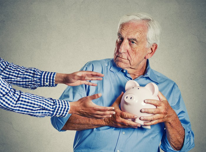 A senior man protects a piggy bank from someone trying to get it.