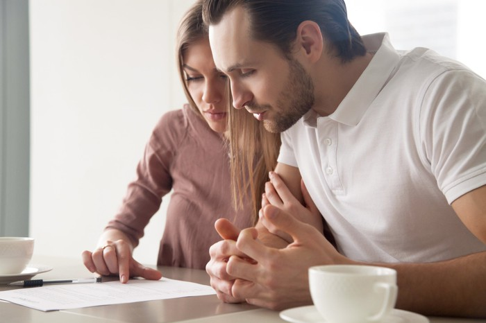 Young couple looking at a document.