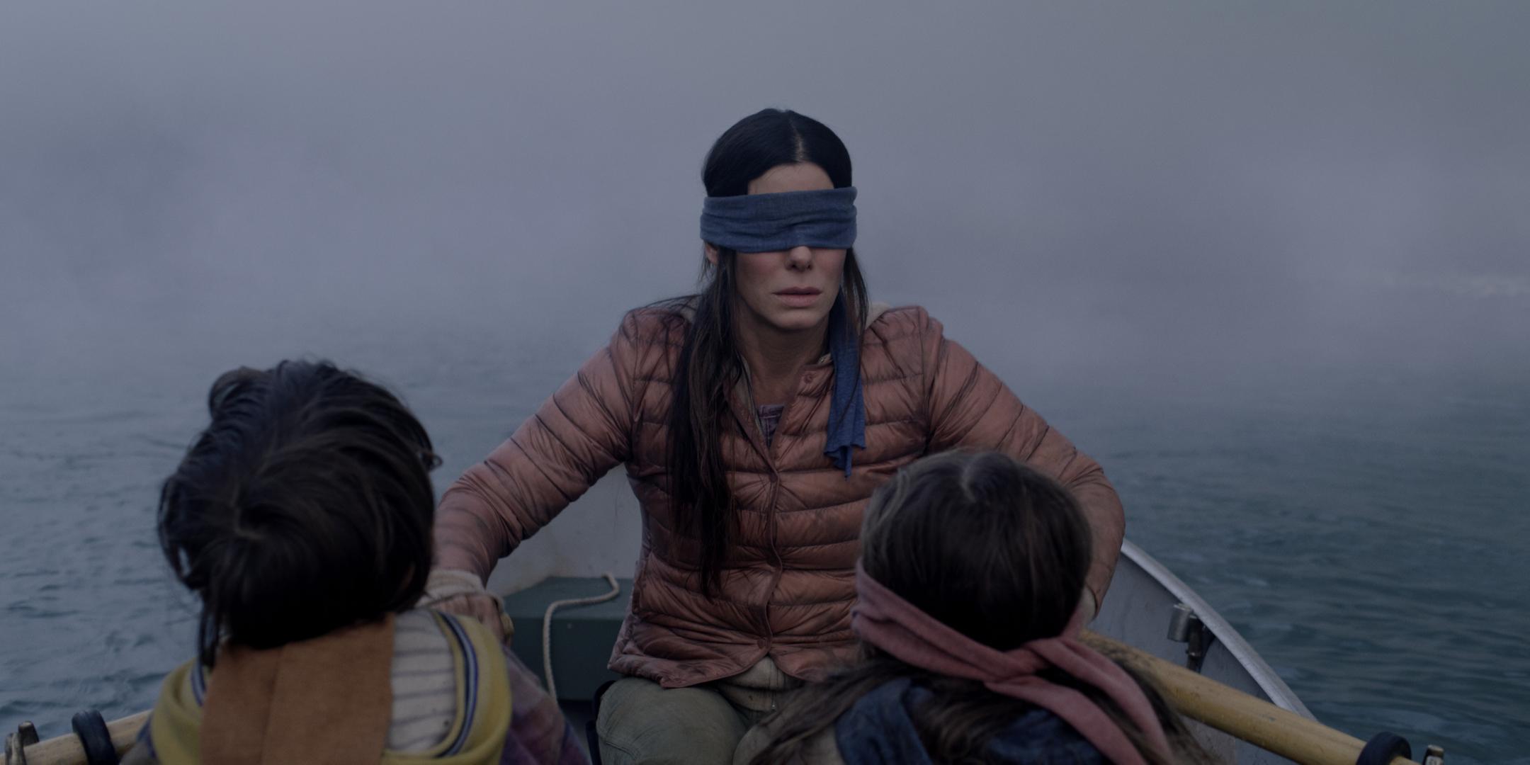 Sandra Bullock rowing a boat wearing a blindfold in a scene from Netflix original movie Bird Box.