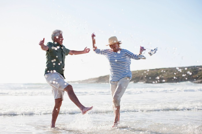 A senior couple splashes happily in the ocean on a beach.
