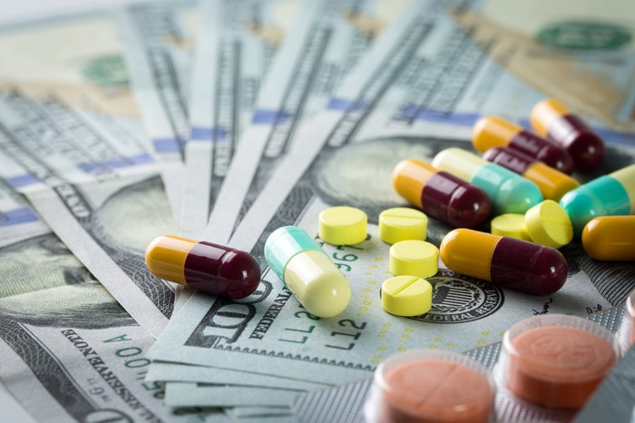 A colorful assortment of pills and capsules is spread out over a pile of U.S. hundred-dollar bills.